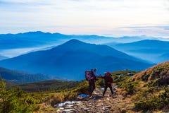 2 Hikers помогая одину другого на горной тропе Стоковые Изображения