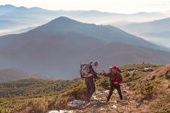 2 Hikers помогая одину другого на горной тропе Стоковые Изображения RF