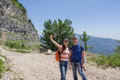 Hikers принимая фото с умным телефоном в горном пике Стоковые Изображения