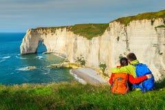 Hikers при рюкзак, наслаждаясь океаном, Etretat, Нормандия, Франция Стоковые Фотографии RF