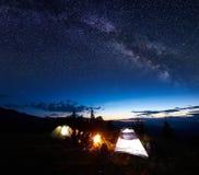 Hikers семьи имея остатки на ноче располагаясь лагерем в горах Стоковое Изображение
