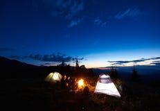 Hikers семьи имея остатки на ноче располагаясь лагерем в горах Стоковая Фотография RF