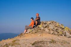 Hikers сидят на верхней части горы и смотрят VI Стоковые Изображения RF