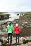 Hikers смотря природу Исландии водопадом Стоковые Изображения