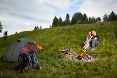 Hikers соединяют сидят на траве около шатра и лагерного костера Стоковая Фотография