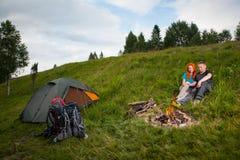 Hikers соединяют сидят на траве около шатра и лагерного костера Стоковые Изображения