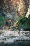 Hikers стоя на другом банке реки горы Стоковая Фотография RF