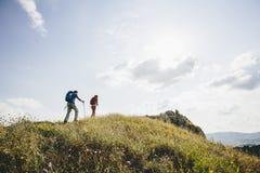 Hikers с рюкзаками идя na górze горы и наслаждаются hik Стоковая Фотография RF