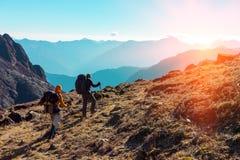 Hikers с рюкзаками идя в горы к восходящему солнцу Стоковое Изображение
