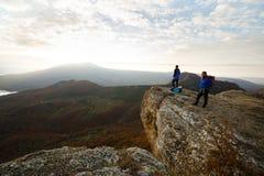 2 hikers с рюкзаками стоят на верхней части горы и смотреть красивый желтый заход солнца ландшафта осени сверх Стоковые Фотографии RF