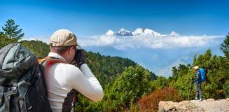 Hikers с рюкзаками фотографируют к предпосылке гор Стоковые Изображения RF