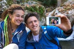 2 Hikers человек и девушка принимая фото с мобильным телефоном Стоковая Фотография RF