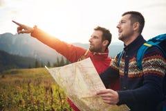 Hikers читая след составляют карту пока trekking в холмах Стоковая Фотография RF