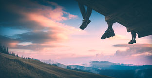Hikers above the valley. Instagram stylisation. Hikers sit on a wooden flooring above the carpathian mountain valley and enjoy colorful clouds in a light of Stock Photography