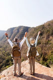 Hikers arms open. Mid age hikers arms open on mountain cliff stock images