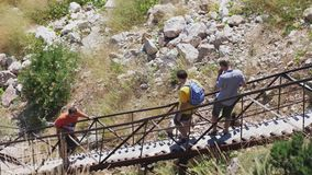 Russia, Crimea, 5 july 2017. Hikers with backpack walking up some steps. slow motion. 3840x2160 stock footage