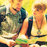 Hikers backpackers couple reading map on trip. Royalty Free Stock Images