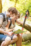 Hikers backpackers couple reading map on trip. Stock Images