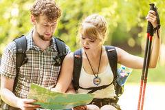 Hikers backpackers couple reading map on trip. Stock Image