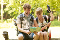 Hikers backpackers couple reading map on trip. Royalty Free Stock Photography