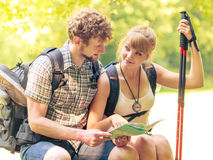 Hikers backpackers couple reading map on trip. Royalty Free Stock Photo