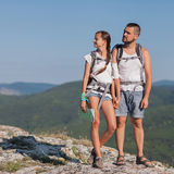 Hikers with backpacks. Enjoying valley view from top of a mountain Royalty Free Stock Images