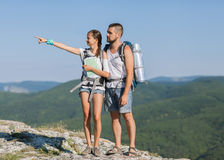 Hikers with backpacks. Enjoying valley view from top of a mountain Stock Image