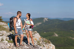 Hikers with backpacks. Enjoying valley view from top of a mountain Royalty Free Stock Image