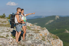 Hikers with backpacks. Enjoying valley view from top of a mountain Stock Photos