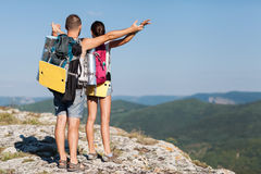 Hikers with backpacks enjoying valley view from top of a mountain. The concept of freedom Stock Photos