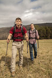 Hikers with backpacks in field. Two hikers with backpacks and walking sticks walking to the campsite stock images
