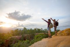 Hikers with backpacks relaxing on top of a mountain and enjoying stock photos