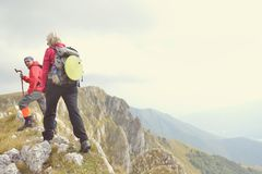 Hikers with backpacks relaxing on top of a mountain and enjoying the view of valley Stock Images