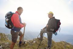 Hikers with backpacks relaxing on top of a mountain and enjoying the view of valley Royalty Free Stock Images