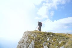 Hikers with backpacks relaxing on top of a mountain and enjoying the view of valley Royalty Free Stock Image
