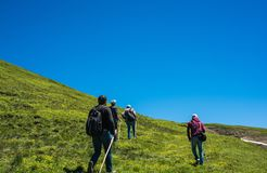 Hikers with backpacks and trekking poles walking in Artvin highland. Hikers with backpacks and trekking es walking in Turkish highland royalty free stock photography