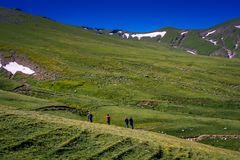 Hikers with backpacks and trekking poles walking in Artvin highland. Hikers with backpacks and trekking poles walking in Turkish highland royalty free stock photography