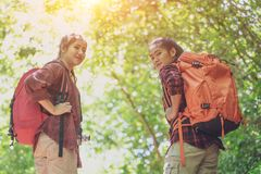 Hikers with backpacks walking through a meadow with lush grass. Two young Asian female hipster hiking on mountain holiday. royalty free stock photos