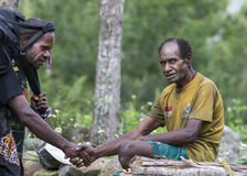 Hikers in Baliem Valley. Baliem Valley, West Papua, Indonesia, February 12th, 2016: Hiker meeting a local man in Baliem Valley royalty free stock images