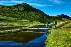 Hikers and bridge over creek, trekking in Iceland Stock Image