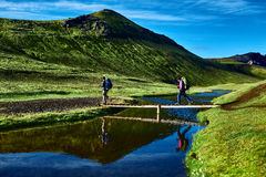 Hikers and bridge over creek, trekking in Iceland Royalty Free Stock Photos