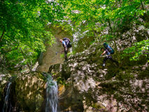 Hikers climb the rocks near the waterfall Royalty Free Stock Photography