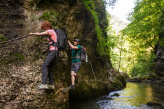 Hikers climbing above the river Stock Images