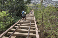 Hikers climbing down wooden rail cart bridge of KoKo Crater, Oah Stock Photos