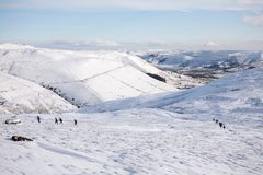 Hikers climbing Kinder Scout in snow Stock Photo