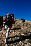 Hikers climbing the mountain. Group of hikers climbing up the rocky mountain Stock Image