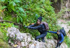 Hikers climbing on mountain wall Stock Photography