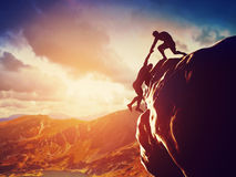 Hikers climbing on rock, giving hand and helping to climb. Hikers climbing on rock, mountain at sunset, one of them giving hand and helping to climb. Help Royalty Free Stock Photo