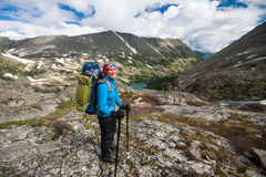 Hikers are climbing rocky slope of mountain Stock Photo