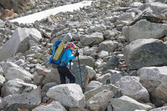 Hikers are climbing rocky slope of mountain Stock Images